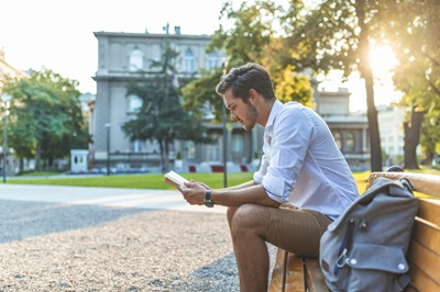young college male student studying on bench
